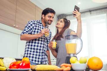 healthy and eco lifestyle.happy indian woman with her husband making smoothie in big kitchen,taking photos portrait on smartphone camera