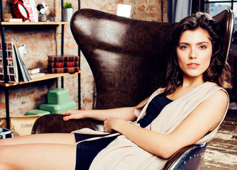 young pretty woman waiting alone in modern loft studio, fashion clothers wearing hat, lifestyle and people home concept