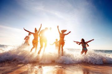 Big group happy friends runs and having fun at sunset beach Fototapete