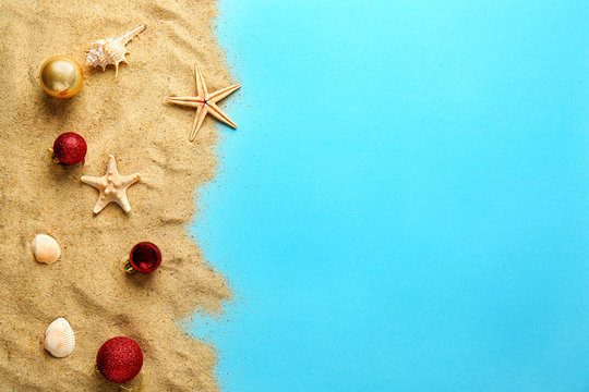 Beach sand with Christmas balls on color background
