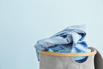 Basket with dirty laundry on color background