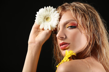Beautiful sexy young woman with gerbera flowers on dark background