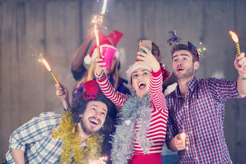 multiethnic group of casual business people taking selfie during new year party