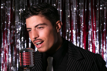 Handsome latino singer performs in front of vintage microphone in nightclub