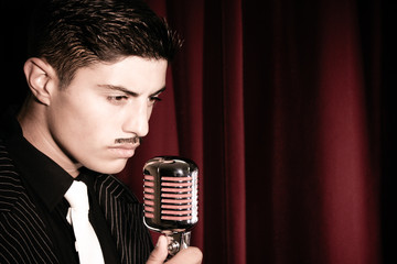 Handsome latino singer performs in front of vintage microphone in nightclub with red curtain in background