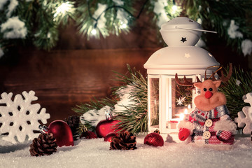 White lantern with a burning candle stands in the snow surrounded by Christmas decorations on the background of a wooden wall, Christmas tree branches and lights
