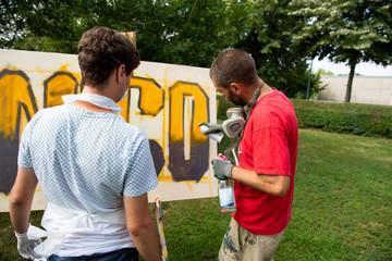 Graffiti Workshop Leiter zeigt Teilnehmer Sprühtechnik mit Spraydose
