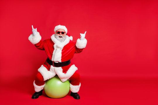 Full length body size view of his he nice attractive cheerful cheery glad fat bearded Santa working out sitting on pilates ball showing horn sign heavy metal isolated over bright vivid shine red