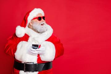 Portrait of cheerful santa claus in hat looking dreamy using cell phone plan newyear party wearing belt eyewear eyeglasses isolated over red background