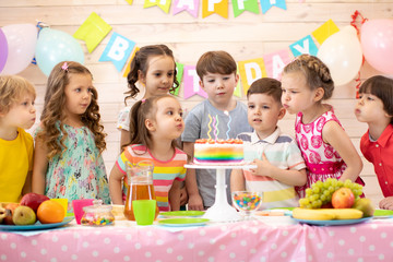 Happy children at table celebrating birthday holiday. Kids blows together candles on festive cake