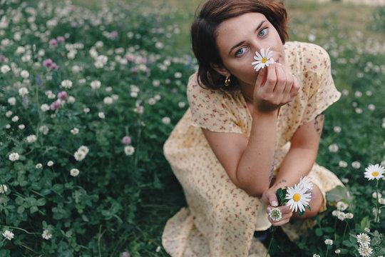 Portrait of young woman holding daisy in field