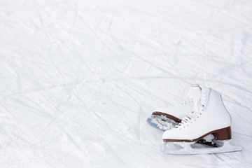 close up of figure skates and copy space over ice with marks from skating