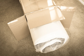 Filtered image close-up roll-packed spring mattresses unbox on carpet floor background