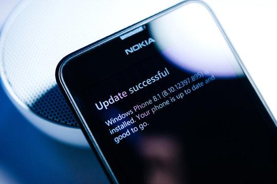 PARIS, FRANCE - JAN 7, 2016: Update successful message on Windows Microsoft Nokia Lumia Surface smartphone telephone - blue technology tone