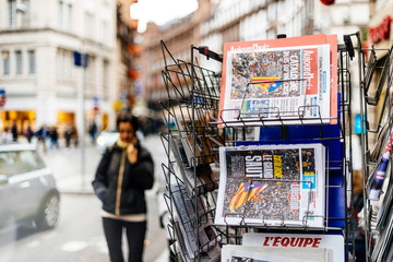 PARIS, FRANCE - OCT 28, 2017: Pedestrians next to French international newspaper with news from Spain about the Catalonia Referendum and protests in Barcelona - kiosk stand in city