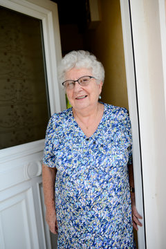 elderly senior woman opening front door of house and welcoming people at home