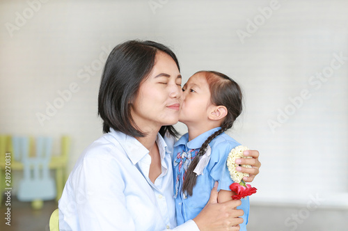 Portrait Asian little girl kissing her mom and hugging on Mother's day in thailand. Kid Pay respect and give Thai traditional jasmine garland to mother.