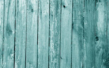 Weathered wooden fence in cyan color.