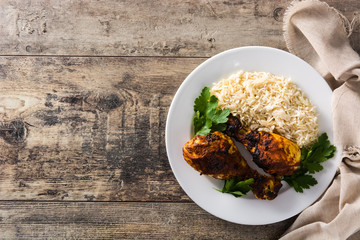 Roasted tandoori chicken with basmati rice in plate on wooden table. Top view. Copy space