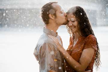 Couple in love hugging and kissing under he rain. They are wet and smiling Wall mural