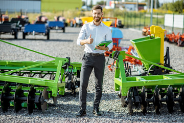 Portrait of a handsome salesman standing near the plow at the outdoor ground of the shop with new agricultural machinery Fotomurales