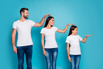 Profile side photo of sweet parent and their daughter with brunet hair holding hand looking wearing white t-shirt denim jeans isolated over blue background
