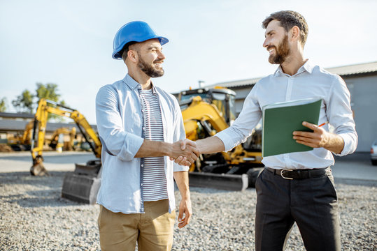 Builder choosing heavy machinery for construction with a sales consultant shaking hands on the open ground of a shop with special vehicles