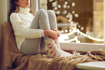childhood, sadness and people concept - sad beautiful girl in sweater sitting on sill at home window over christmas lights background