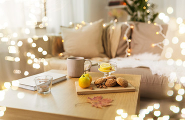 Fototapete - hygge and cozy home concept - oatmeal cookies, book, tea and lemon on wooden table in living room