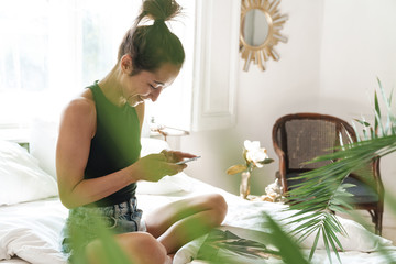 Portrait of joyous woman holding cellphone while reading magazine on bed in bright room with green plant