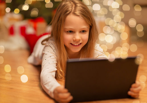 christmas, holidays and childhood concept - smiling girl with tablet pc computer at home