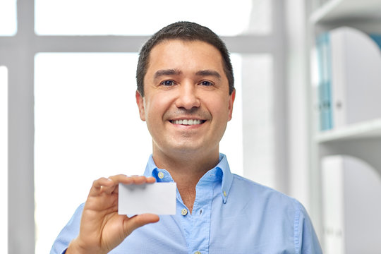 business and people concept - smiling middle-aged businessman showing visiting card at office