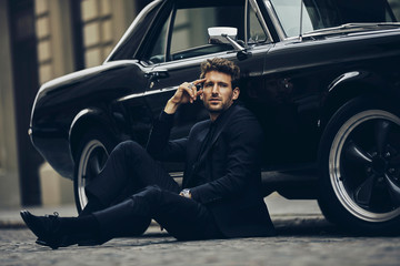 Handsome man in black suit sitting on the street near his old classic car