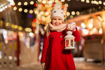holidays, childhood and people concept - happy little girl with lantern at christmas market in winter evening