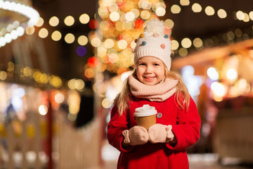 holidays, childhood and people concept - happy little girl with cup of tea at christmas market in...