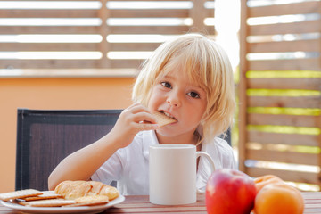 Child bites cookie at snack or breakfast