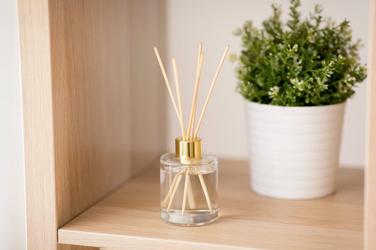 aromatherapy and home perfume concept - aroma reed diffuser and pot flower on wooden shelf
