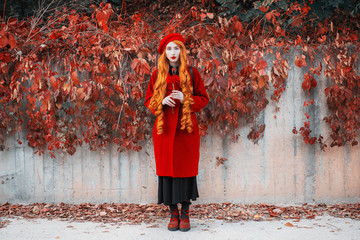 Redhead woman hol flower in red coat on autumn background. Girl on background wall with orange autumn leaves. Red turban and stylish coat. Fashion model with red hair on october background. Long hair