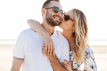 Photo of lovely young woman kissing and hugging handsome man while walking on sunny beach