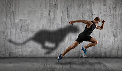 Athletic man sprinter running on dark wall background