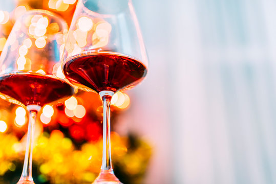 Two glass of red wine in front of christmas tree lights bokeh. New year eve and xmas celebration party.