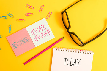 Text sign showing New Monday New Week New Goals. Business photo showcasing goodbye weekend starting fresh goals targets Square blank sticky notepads pencil clips eyeglasses yolk color background