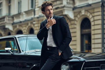 Young handsome man with black classic car wearing black suit