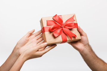Man's and woman's hands isolated over white wall background holding present gift box.