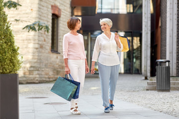 sale, consumerism and people concept - two senior women or friends with shopping bags walking along...