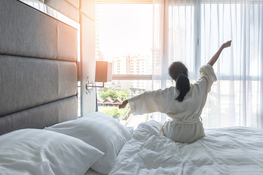 Work-life quality balance concept with lazy lifestyle of Asian girl on bed relaxing in comfort city hotel bedroom, take it easy, resting from good sleep waking up on weekend morning having a good day