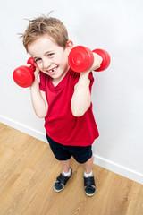 smiling boy expressing fun pride, lifting dumbbells to grow up
