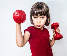 portrait of cheeky pouting child raising dumbbells for feminism