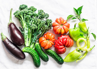 Fresh seasonal vegetables food background. Aubergines, tomatoes, peppers, broccoli on a light background, top view. Flat lay, copy space