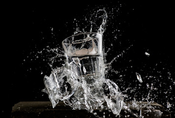 a glass falls on a black background and breaks, two glasses break on a black background